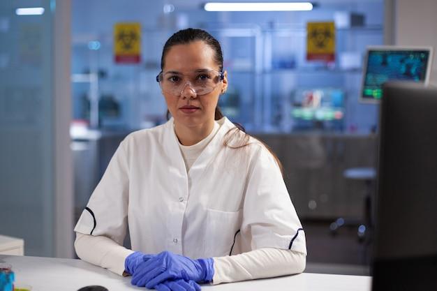 Porträt einer ärztin, die während des biochemischen experiments am tisch sitzt