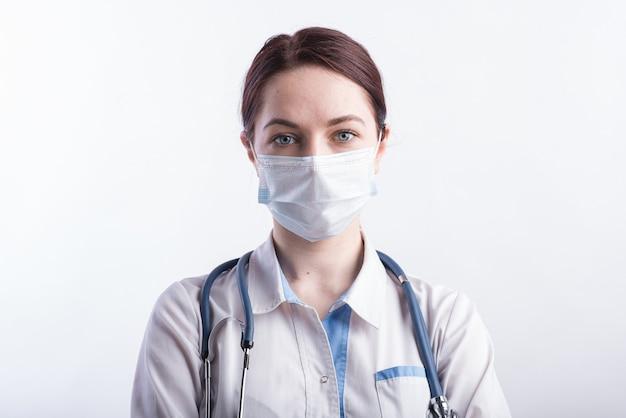Porträt einer ärztin in einer weißen uniform mit einer medizinischen maske auf ihrem gesicht im studio auf einem weißen hintergrund