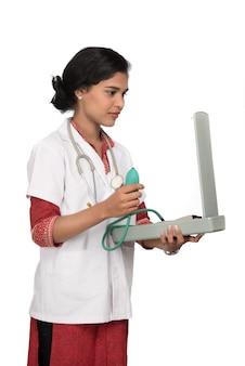 Porträt einer ärztin mit blutdruckinstrument und stethoskop auf weißem hintergrund.