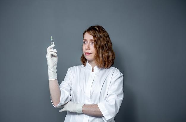 Porträt einer ärztin mit einer spritze in den händen