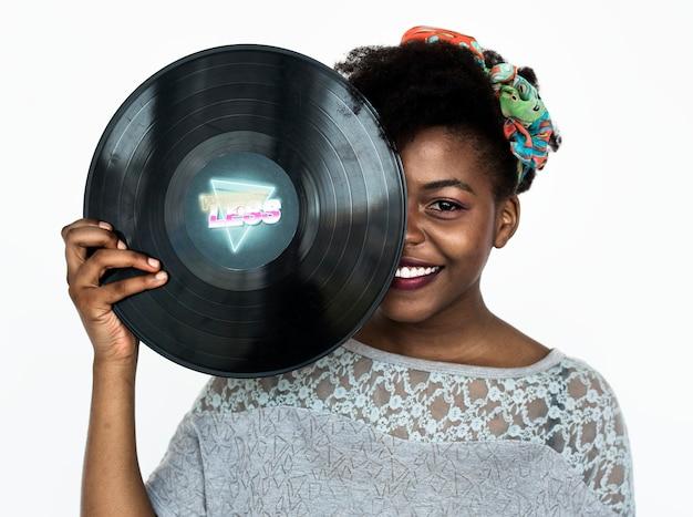 Porträt einer afrikanerin, die eine schallplattenaufzeichnung anhält