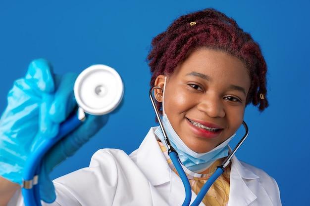 Porträt einer afrikanischen ärztin im laborkittel mit gesichtsmaske und stethoskop vor blauem hintergrund
