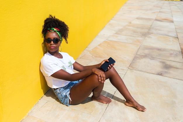 Porträt einer afrikanischen frau im t-shirt, das mit telefon sitzt, während er sich auf eine gelbe wand stützt