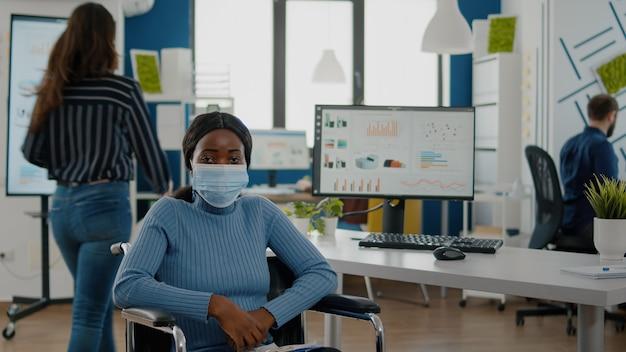 Porträt einer afrikanischen frau mit schutzgesichtsmaske, die auf die kamera schaut, die im rollstuhl sitzt, während...