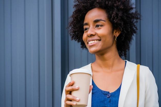 Porträt einer afro-geschäftsfrau, die eine tasse kaffee hält, während sie draußen auf der straße steht
