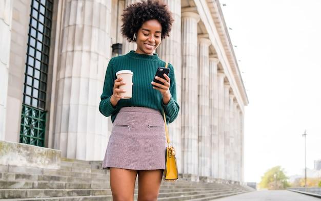 Porträt einer afro-geschäftsfrau, die ihr handy benutzt und eine tasse kaffee hält, während sie im freien auf der straße spazieren geht