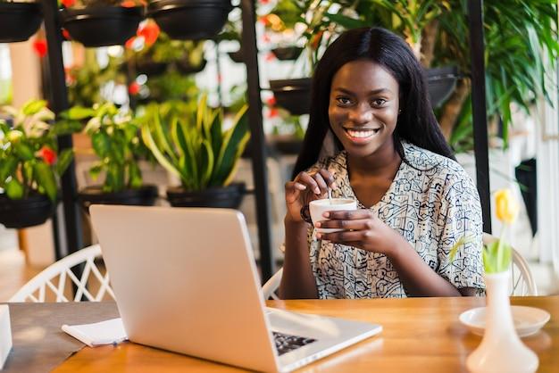Porträt einer afroamerikanerfrau, die im café mit laptop und kaffee entspannt