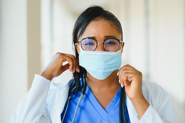 Porträt einer afroamerikanischen ärztin in schutzmaske im krankenhaus