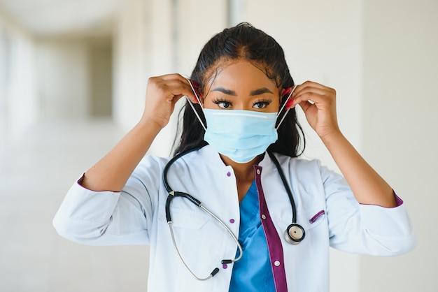 Porträt einer afroamerikanischen ärztin mit maske, die im krankenhausflur steht. medizin, gesundheit und gesundheitsdienste während der coronavirus-covid-19-pandemie.