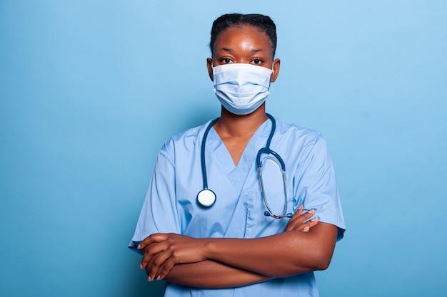 Porträt einer afroamerikanischen arztkrankenschwester, die eine schützende gesichtsmaske trägt