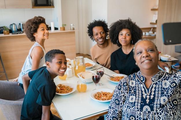 Porträt einer afroamerikanischen familie mit mehreren generationen, die ein selfie zusammen mit dem mobiltelefon beim abendessen zu hause nimmt. familien- und lifestyle-konzept.