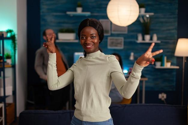 Porträt einer afroamerikanischen frau, die spät in der nacht im wohnzimmer in die kamera lächelt und ein victory-handzeichen zeigt. im hintergrund versammeln sich multiethnische freunde, die während der wochenendparty spaß haben.