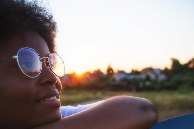 Porträt einer afroamerikanischen frau vor dem hintergrund eines sonnenuntergangs, nahaufnahme.