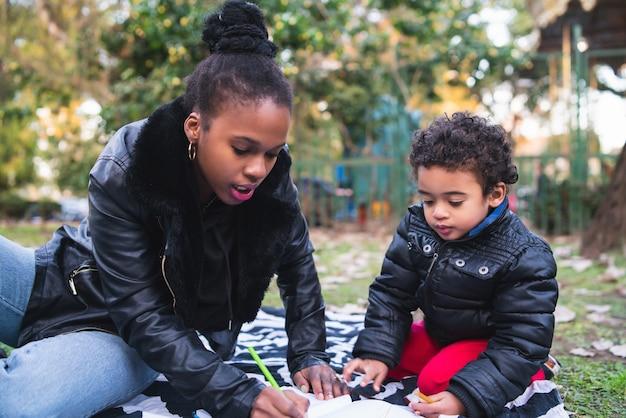Porträt einer afroamerikanischen mutter mit seinem sohn, der draußen im park zusammen spielt und spaß hat. monoparentale familie.