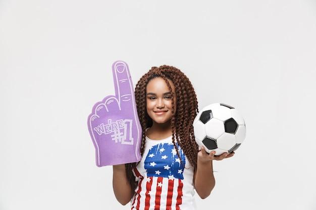 Porträt einer aktiven frau, die einen ventilatorhandschuh und einen fußball hält, während sie isoliert gegen die weiße wand steht