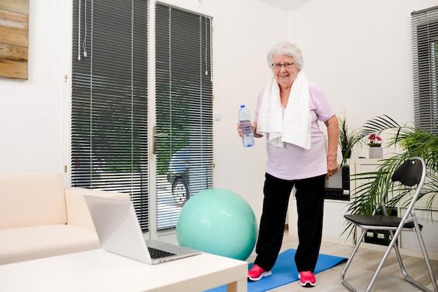 Porträt einer aktiven und dynamischen älteren frau, die zu hause sportfitness macht und eine mineralwasserflasche hält