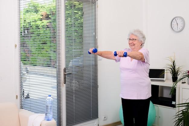 Porträt einer aktiven und dynamischen älteren frau, die zu hause sportfitness macht