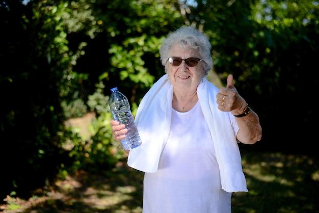 Porträt einer aktiven und dynamischen seniorin, die sport fitness im freien in grüner natur macht und eine mineralwasserflasche hält
