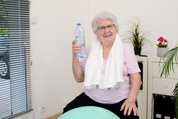 Porträt einer aktiven und dynamischen seniorin, die zu hause sportfitness macht und eine flasche mineralwasser hält
