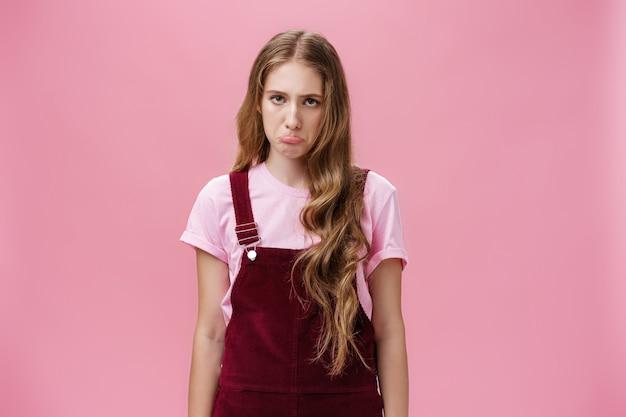 Porträt einer albernen, unzufriedenen und unruhigen, süßen jungen frau in overalls, die schmollend und schmollend ist und ein düsteres gesicht verliert oder einen schlechten tag hat, der verärgert und traurig über rosafarbenem hintergrund steht. emotionen konzept