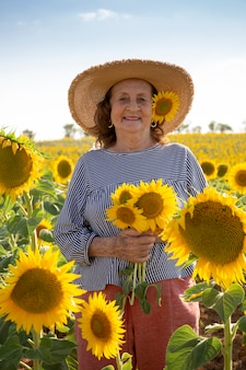 Porträt einer alten frau mit sonnenblumen in ihren händen.