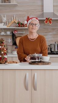 Porträt einer alten frau mit weihnachtsmütze, die die weihnachtszeit in der dekorierten küche feiert