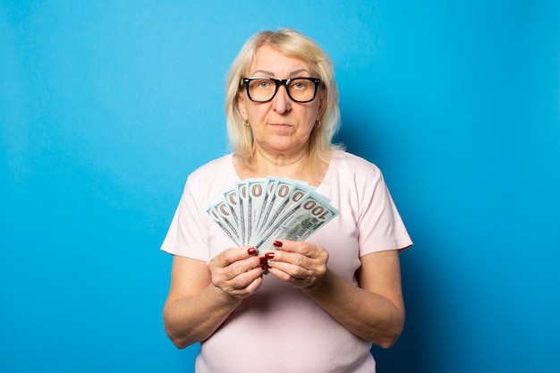 Porträt einer alten freundlichen frau im lässigen t-shirt und in den gläsern, die geld in ihren händen auf einer isolierten blauen wand halten. emotionales gesicht. konzept wohlstand, gewinn, kredit, rente