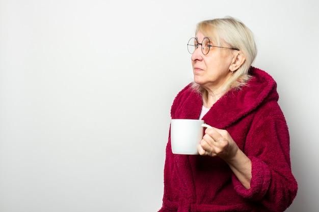 Porträt einer alten freundlichen frau in einem lässigen morgenmantel und in den gläsern, die eine tasse auf einer isolierten hellen wand halten. emotionales gesicht. morgenkaffee-konzept