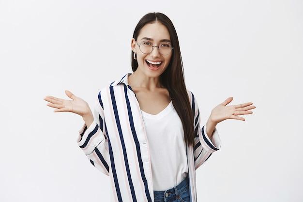 Porträt einer amüsierten, gut aussehenden, sorglosen studentin in einem stilvollen gestreiften hemd und einer brille, die die handflächen beiseite spreizt, während sie breit lächelt und den sozialen lebensstil führt