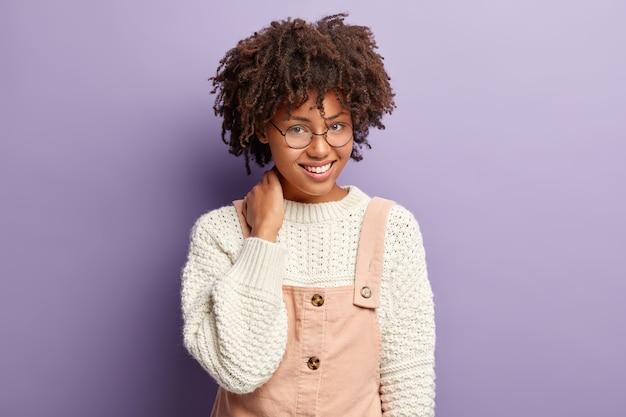 Porträt einer angenehm aussehenden dunkelhäutigen frau mit afro-haarschnitt, hält die hand am hals und ist gut gelaunt