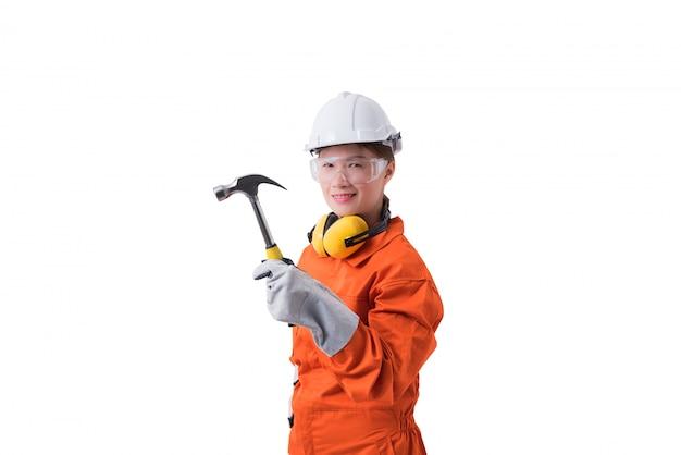 Porträt einer arbeitnehmerin im mechaniker jumpsuit hält den hammer, der auf weißem hintergrund lokalisiert wird