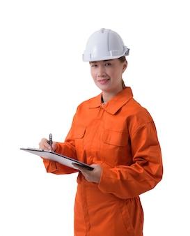 Porträt einer arbeitnehmerin im mechaniker jumpsuit hält klemmbrett