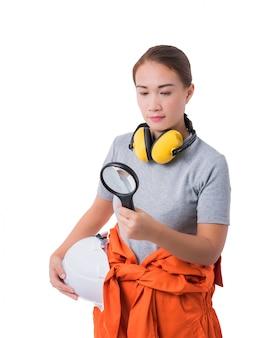 Porträt einer arbeitnehmerin in der mechaniker-overallhand, die lupe hält