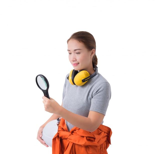 Porträt einer arbeitnehmerin in mechaniker jumpsuit-hand, die lupe hält