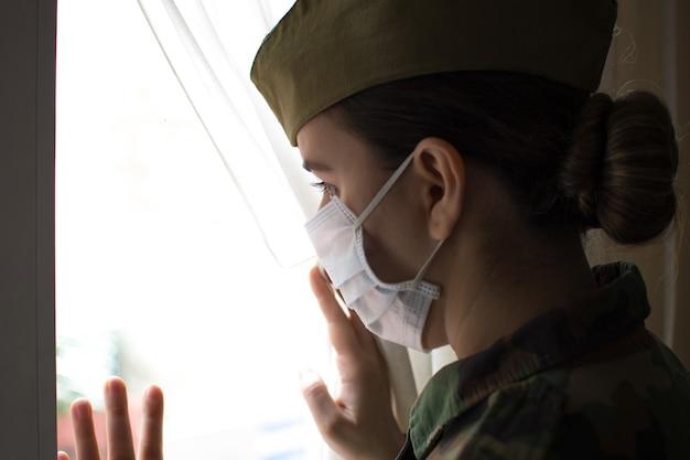 Porträt einer armeeoffizierin in uniform und operationsmaske. aus dem fenster schauen