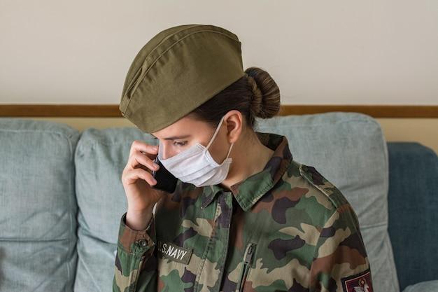 Porträt einer armeeoffizierin in uniform und operationsmaske. mit dem handy sprechen