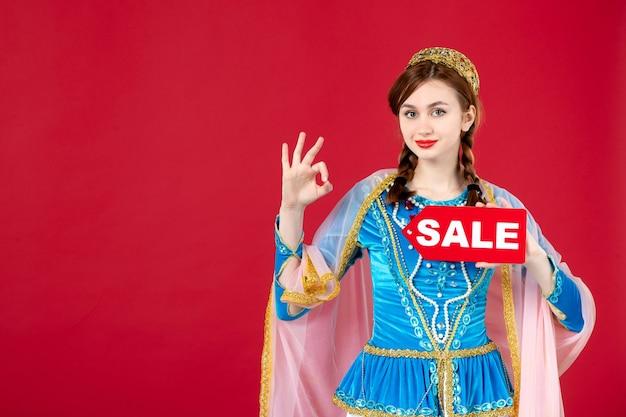 Porträt einer aserbaidschanischen frau in traditioneller kleidung, die das typenschild des verkaufs auf rot hält