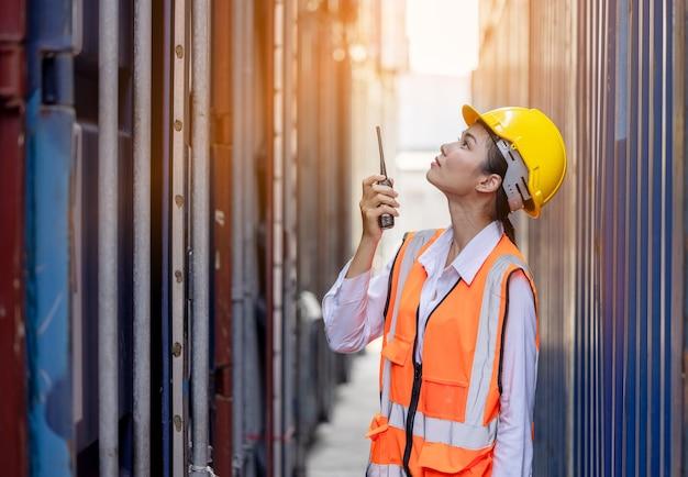 Porträt einer asiatischen arbeiterin in sicherheitsuniform, die mit walkie-talkie im containerlager spricht.