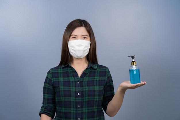 Porträt einer asiatischen frau, die eine chirurgische gesichtsmaske trägt und alkoholgel oder händedesinfektionsmittel präsentiert