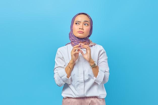 Porträt einer asiatischen frau, die mit unruhigem ausdruck an etwas denkt