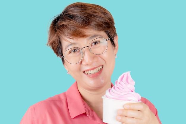 Porträt einer asiatischen frau glückliches halten des eises lokalisiert auf einem farbhintergrund