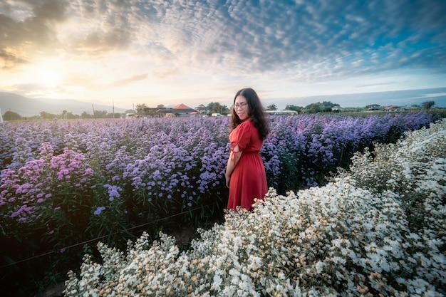 Porträt einer asiatischen jungen frau, die glückliche reisende mit rotem kleid genießt, die in weiß blühendem oder violettem michaelmas-gänseblümchen-blumenfeld genießt, um einen blumenkorb im naturgarten von chiang mai, thailand, zu halten