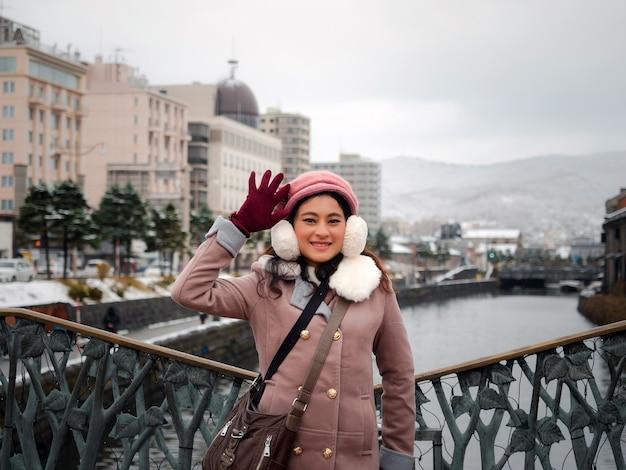 Porträt einer asiatischen touristin in winterkleidung, mantel und pelz mit baskenmütze, die auf der brücke am otaru-kanal steht, berühmter reiseort in hokkaido, japan, mädchen glücklich auf der reise im winter