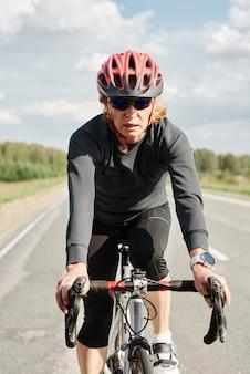 Porträt einer athletin mit helm, die während ihres sporttrainings auf einem fahrrad entlang der straße fährt