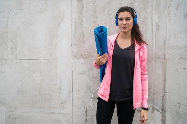 Porträt einer athletischen frau, die eine trainingsmatte hält, während musik hört.