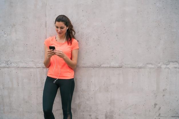 Porträt einer athletischen frau, die ihr handy in einer trainingspause benutzt. sport und gesundheit lebensstil.