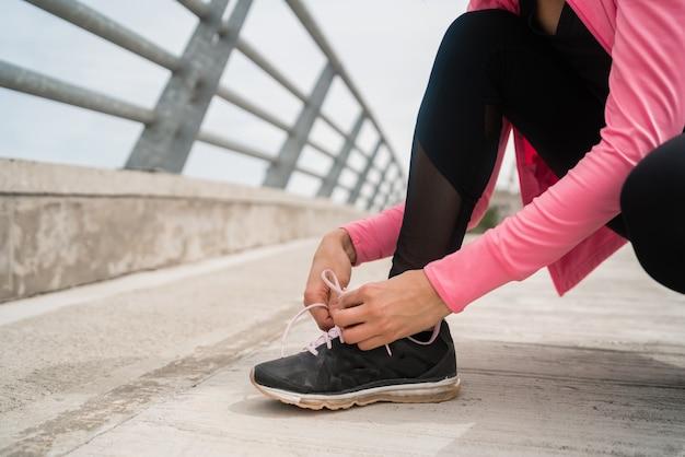 Porträt einer athletischen frau, die ihre schnürsenkel bindet und sich zum joggen im freien bereit macht. sport und gesunder lebensstil konzept.