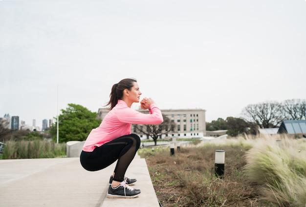 Porträt einer athletischen frau, die übung am park im freien tut. sport und gesunder lebensstil konzept.