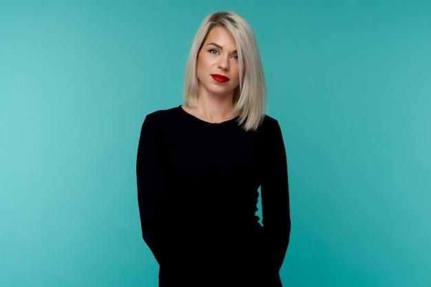Porträt einer attraktiven blonden frau in einem schwarzen kleid. schönes mädchen, das auf einem blauen hintergrund aufwirft.
