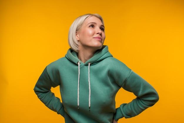 Porträt einer attraktiven blondine mit kurzen haaren, die an einer leuchtend gelben wand steht und nach oben schaut